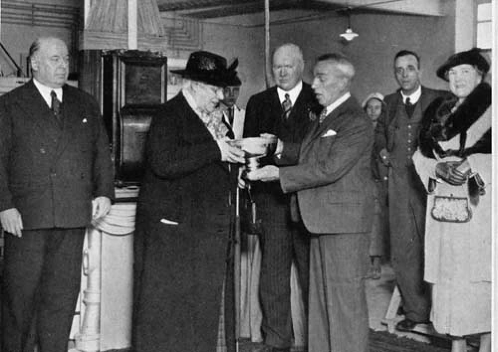 Miss E. Aitken being presented with a rose bowl at the opening of the new bottling hall in 1938.